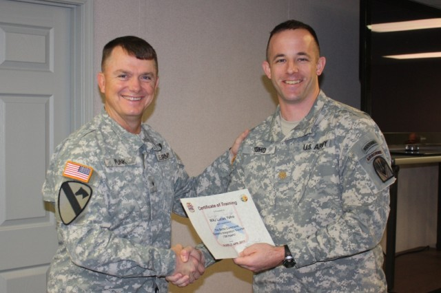 Brigadier General Paul E. Funk II (left) presents a course completion certificate to Major Lucas Yoho during a Battle Command System Integration graduation ceremony. Yoho was one of 13 Joint Readiness Training Center trainer-mentors in the class.