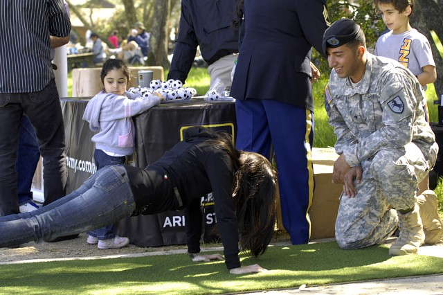 Spc. Steven Ganji, an interpreter for the Army, counts push-ups for a prospect during Persian Nature Day in Sacramento, Calif.