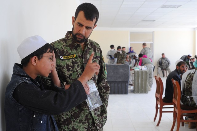 """PAKTYA PROVINCE, Afghanistan - Afghan National Army Capt. Haarwn Amin give an eye exam during a medical outreach mission at the Gardez City Orphanage compound, April 26. Some of the children would be blind without glasses said U.S. Army Capt. Benjamin Uhl, optometrist from Sioux City, Iowa, with the 591st Medical Logistics Unit and.  (Photo by U.S. Air Force Staff Sgt. Barry Loo, Paktya Provincial Reconstruction Team Public Affairs)"""""""