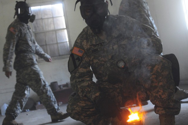 Sergeant First Class Phillip Odum, HHC, 1HBCT, sets fire to the Captor Spray inside the Gas Chamber on Fort Stewart, April 21.