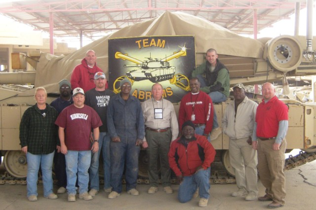 Anniston Army Depot employees pose in front of a M1 Abrams tank in Baghdad.