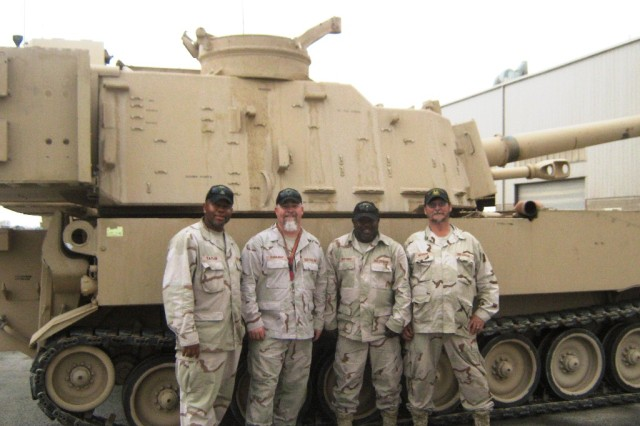 The Paladin FAASV repairers from Anniston Army Depot take a photo in front of one of their vehicles in Baghdad.