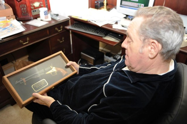 Lee Hayslette, a retired sergeant major who served at Anniston Army Depot, holds a pistol he received in appreciation of his time in service.