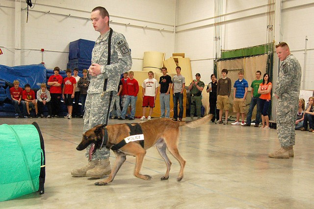 STEVENS POINT, Wis. -- Sgt. Timothy Burr, a dog handler from the 217th Military Police Detachment, Fort Lee, Va., demonstrates dog commands during Pathway to Success at Stevens Point Area Senior High on Wednesday, April 13. Spc. Patrick Robinson, 217th MP Det., explains the law enforcement capabilities of Nico, a Belgian malinois, throughout the demonstration.