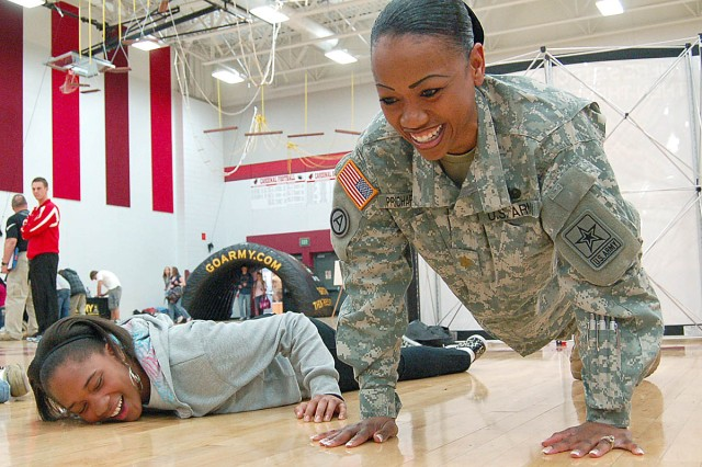 FOND DU LAC, Wis. -- Maj. Clydea Prichard-Brown, Milwaukee Recruiting Battalion executive officer, encourages a student to keep up with her during a physical fitness challenge. The goal is to do as many push-ups as possible within 60 seconds.