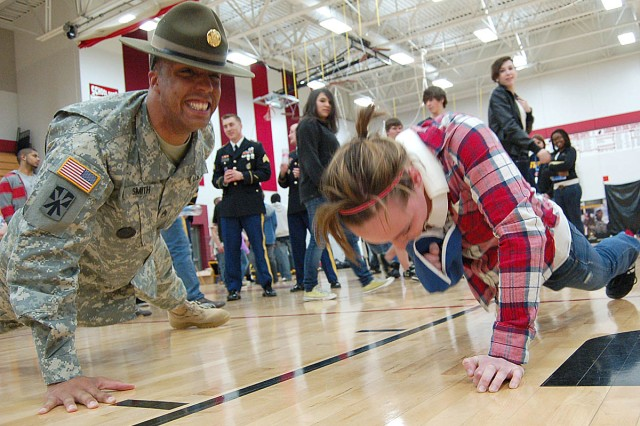 FOND DU LAC, Wis. -- Staff Sgt. Jason Smith, an Accessions Support Brigade drill sergeant, keeps up with a Fond du Lac High School student Friday, April 15. Smith challenged students to showcase their strength during a fitness promotion run by Milwaukee Recruiting Battalion.