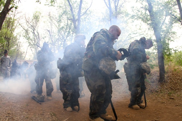 FORT SILL, Okla. -- Gas! Gas! Gas! Soldiers in A Battery, 1st Battalion, 19th Field Artillery quickly put on their gas masks as smoke simulates a nuclear, biological or chemical attack.