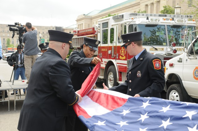 Members of the Arlington County Fire Department respectfully fold the American Flag prior to a ceremony held in honor of the members of the FBI Washington Field Office who responded after the terrorist attack on Sept. 11, 2001 at the Pentagon.   The Washington Field Office, together with the Joint Force Headquarters National Capital Region/U.S. Army Military District of Washington, hosted a ceremony 28 April, to commemorate the permanent placement of a piece of stone recovered from the Pentagon after 9/11.