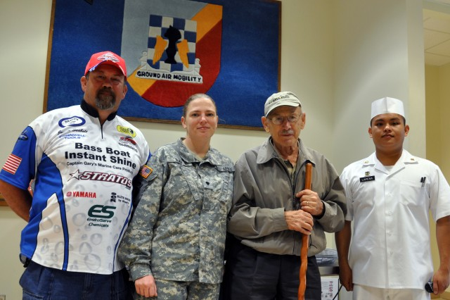 "(L-R) James Seabolt, a professional bass angler from Newton Grove, N.C.; Spec. Taunya Ray, of Myrtle Beach, S.C., a motor vehicle operator assigned to Headquarters, 2nd Battalion, 82nd Combat Aviation Brigade (CAB); World War II B-17 bombadier, Roger Rogers; and Spec. Michael Lapena, of Davalo City, Phillipines, a food service specia...list assigned to 1st Battalion, 82nd CAB, pose for a photograph, April 28, 2011, at the 82nd CAB Dining Facility - ""The Pegasus Inn"". Seabolt and Rogers are taking part in the 6th Annual ""Warriors on the Water"" fishing tournament at Jordan Lake, N.C., April 29."