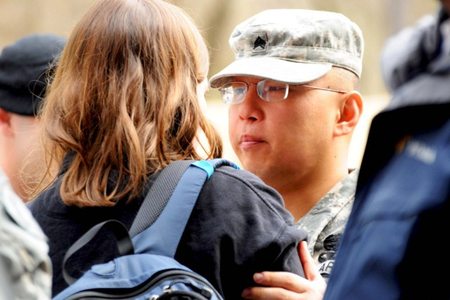 Sgt. Joseph Cush, a Civil Affairs Sgt., shares a moment with his wife, Emily, following a deployment ceremony for Bravo Company of the 443rd Civil Affairs Battalion in Warwick, R.I. on April 14, 2011. This year-long tour to Afghanistan will be Cush's fourth deployment since September 11, 2001. This will be Cush's first time experiencing a deployment with a family and a newborn baby, Julia. Following the deployment ceremony, Bravo Company Soldiers boarded a bus to Fort Dix, N.J. where they will conduct pre-mobilization training prior to deploying to Afghanistan