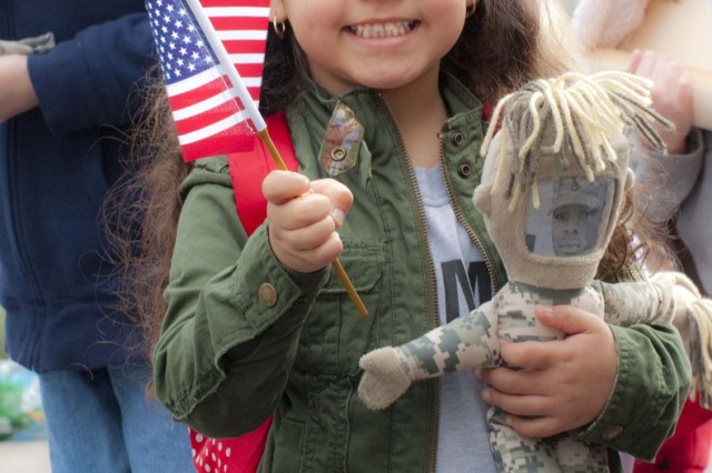 "Kaysi, 4, daughter of Staff Sgt. Kenneth Dillingham, holds her American flag and ""daddy doll"" during a deployment ceremony for Bravo Company of the 443rd Civil Affairs Battalion in Warwick, R.I. on April 14, 2011. Bravo Company will conduct pre-mobilization training at Fort Dix, N.J. before deploying to Afghanistan for a year-long tour."