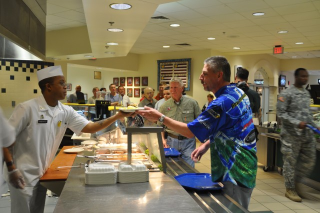 "Pvt. 1st Class Darrin Fisherwater, a food service Soldier assigned to E Co., 2nd Battalion, 82nd Combat Aviation Brigade (CAB),  passes a plate of ""Army chow"" to Rex Johnsonbaugh, a professional bass angler from Altoona, Penn., during the April 28, 2011, breakfast meal at the ""Pegasus Inn"" - the dining facility for the 82nd CAB at Fort Bragg, N.C. Johnsonbaugh brought his bass boat to the post and will take a Soldier ""co-angler"" fishing at Jordan Lake, N.C,  during the 6th Annual ""Warriors on the Water"" fishing tournament, April 29.  More than 150 fisherman will launch their boats in the tournament, each with a service member aboard angling for bass fishing glory."