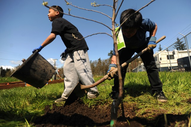 Ikena Tarape, 11, left, and Ian Teodoro, 9, plant an apple tree April 19,  at the JBLM Community Garden. In honor of Earth Day, people from the JBLM community took part in many activities aimed at improving the environment.