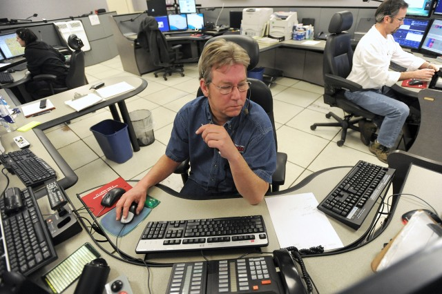 """Kevin Sibbitt, Joint Base Emergency Communication Center supervisor, listens to a 9-1-1 call during his shift last week. """"You never know what's going to happen when the phone rings, says Sibbitt, who's been working as a 9-1-1 dispatcher"""
