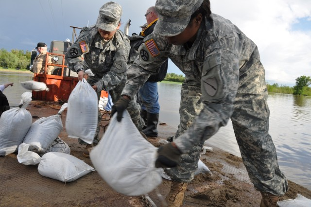 Kentucky Guard members Spc. Tia Brooks and Sgt. Victoria Evans, 2113th Transportation Company, unload sandbags from flat-bed truck for a flood relief mission in Oscar, Ky., April 27, 2011.