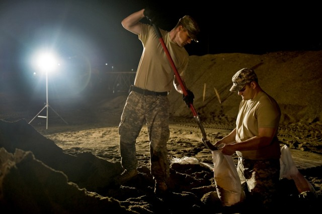 Spc. Benjamin Sukys and Spc. Robert Thorp work through the night filling sandbags at the Indiana Department of Transportation branch in Vincennes, Ind., on April 26, 2011. Sukys and Thorp, both in the Indiana National Guard, are assigned to Company B, 1st Battalion, 151st Infantry Regiment. The Soldiers alternated working six-hour shifts around the clock to fill an order of 100,000 sandbags.