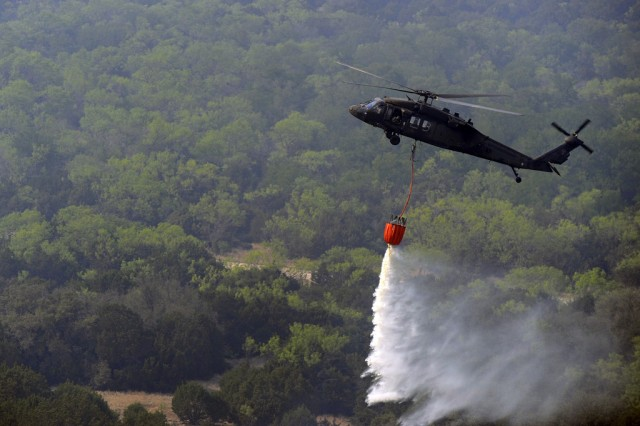 A Texas National Guard Uh-60 Black Hawk helicopter drops water over hot spots. Helicopters were launched out of the Austin Army Aviation Support Facility to help fight the wildfires affecting the Possum Kingdom Lake area in North Texas. The aircraft are equipped with a Bambi Bucket, which carries over 600 gallons of water, to fight fires.