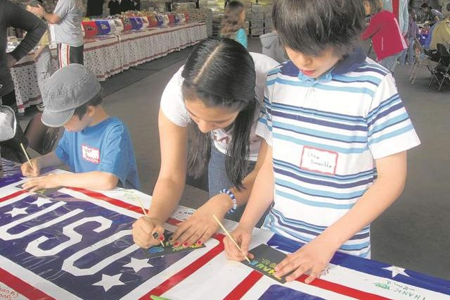 Tyler, Aurora and Evan Bonnette sign thank-you cards to the troops April 21 at the USO warehouse on Fort Belvoir during a Operation USO Care Package stuffing event.