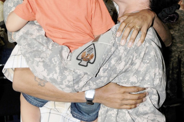 Sgt.  Angelique F. Young embraces her husband, Larry, and son, Jerimiah, April 25 after being deployed a year with the 164th TAOG.