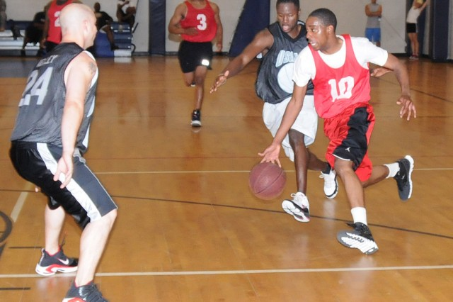 Leonard McKellar, AIT player, runs by L.V. Miller, USAAMC coach and player, during the intramural basketball championship game April 26. AIT took home the championship after dropping the first game, 68-65, but winning the final, 65-57.