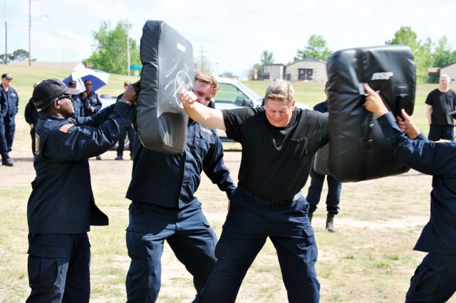 DA security guard Robert Lee runs the gauntlet performing security tasks after being sprayed with pepper spray. Here he is blocking high blows from alleged assailants. Guards must be certified before being allowed to use pepper spray in the field.