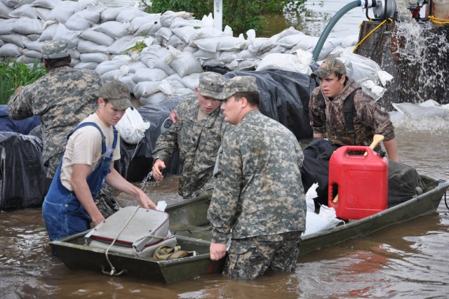 Kentucky National Guard members Army Pfc. David Barrow, Army Spc. Tommy Wyatt and Army Pvt. Cedric Bransford, 2113th Transportation Company, assist local residents in a flood relief mission in Oscar, Ky., April 27, 2011.