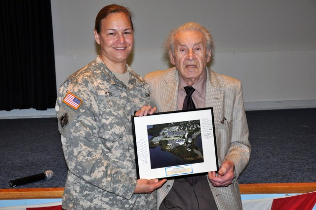Edgar Krasa, a Holocaust survivor, receives a memento from Lt. Col. Kari K. Otto, U.S. Army Garrison-Natick commander, after he spoke there April 28.