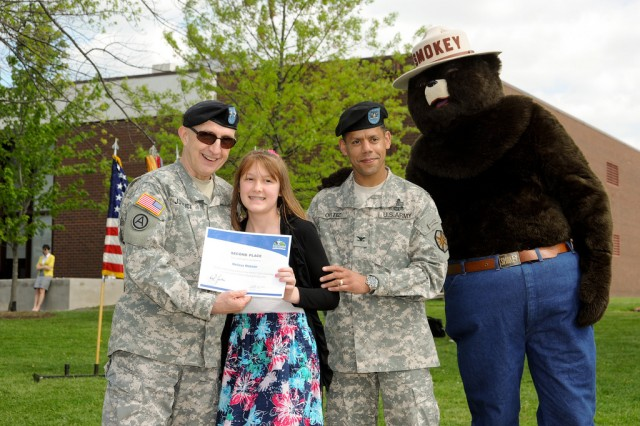 Melissa Webster of St. Joan of Arc School, receives her essay contest award from Maj. Gen. Nick Justice, senior installation commander, Col. Orlando Ortiz, APG garrison commander, and Smokey the Bear.