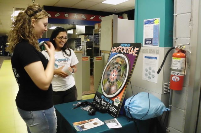 FORT SHAFTER, Hawaii - Sgt. Allyson Layport (left), 8th Theater Sustainment Command, and Summer Rosa-Mullen, SAPRP victim advocate, play the wheel to win prizes at the bowling event, here, April 21.