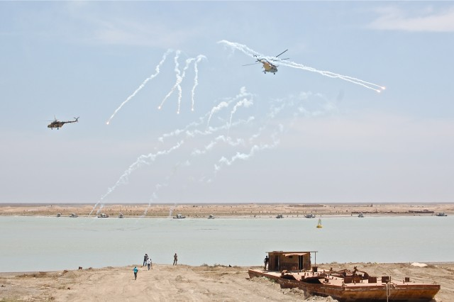Iraqi helicopters provide air support while Iraqi soldiers and sailors assault the far shore in Operation Lion's Leap, a combined-arms, live-fire exercise conducted at Khor az-Zubayr in Iraq's Basrah Province, Apr. 28, 2011. The exercise marked the culmination of months of collective training by Iraqi soldiers, sailors, and airmen, with advise and assistance from Texas National Guardsmen of the 36th Infantry Division.