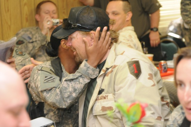 "BAGHDAD - A U.S. Army Soldier shares a hug and a kiss with country music artist Toby Keith during a luncheon at the Robert Hernandez Dining Facility on Forward Operating Base Union III here April 29. Keith spent a few hours with the United States Forces-Iraq's Deputy Commanding General for Advising and Training staff here during his United Service Organizations-sponsored ""Locked And Loaded"" tour."