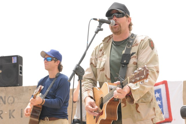 """BAGHDAD - Country music artist Toby Keith performs a short acoustical concert for members of the United States Forces-Iraq's Deputy Commanding General for Advising and Training staff at Forward Operating Base Union III here April 29. Keith spent a few hours with the Deputy Commanding General for Advising and Training staff here during his United Service Organizations-sponsored """"Locked And Loaded"""" tour."""