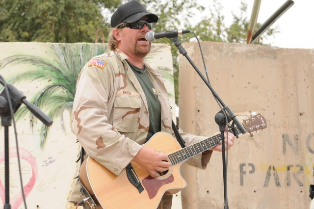 "BAGHDAD - Country music artist Toby Keith performs a short acoustical concert for members of the United States Forces-Iraq's Deputy Commanding General for Advising and Training staff at Forward Operating Base Union III here April 29. Keith spent a few hours with the Deputy Commanding General for Advising and Training staff here during his United Service Organizations-sponsored ""Locked And Loaded"" tour."