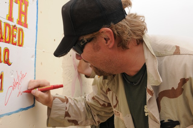 "BAGHDAD - Country music artist Toby Keith leaves his mark on a ""T-Wall"" that serves as a backdrop for the Morale, Welfare and Recreation outdoor stage at Forward Operating Base Union III. Keith spent a few hours with the Deputy Commanding General for Advising and Training staff here during his United Service Organizations-sponsored ""Locked And Loaded"" tour."
