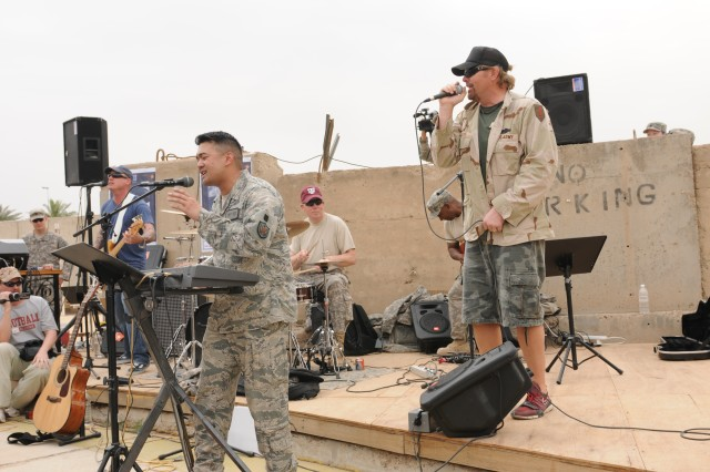 "BAGHDAD - Country music artist Toby Keith rocks out with members of ""MEC"" (""Minimum Essential Chords"") - a band that's made a name for itself here by turning their love for music into a way to relieve deployment stress - as they perform ""Takin' care of Business."" Keith spent a few hours with the Deputy Commanding General for Advising and Training staff here during his United Service Organizations-sponsored ""Locked And Loaded"" tour."