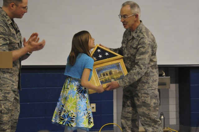 Col. Richard Fischer (right) and 2nd Lt. Nathan Wallin (left) present Mackenzie Frost an American Flag, flown in her honor in Baghdad, Iraq, and a certificate of appreciation, April 19.