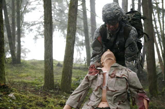 Sgt. Heather Blake positions a simulated battlefied casualty during training for the Expert Field Medical Badge.
