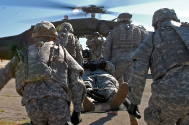 Soldiers carry a simulated casualty to a medevac helicopter.