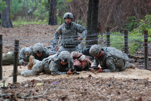 Medics move a patient through a barbed wire obstacle at the combat training lanes of the Camp Bullis Training Site in San Antonio.