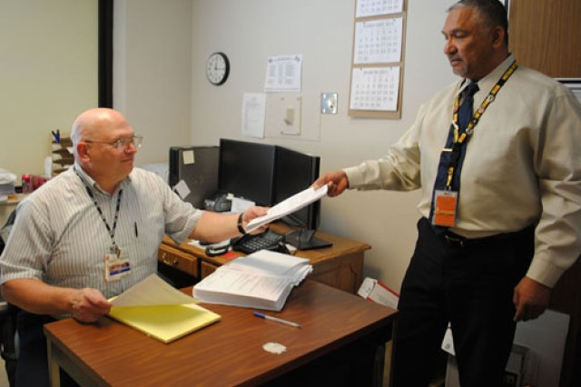 Patrick Davidson (left), a military service coordinator for the Department of Veterans Affairs, accepts a case from Pete Sandoval, a Physical Evaluation Board liaison officer for Irwin Army Community Hospital in Fort Riley, Kan. With VA and PEBLO offices in the same building, the collocation forms a one-stop shop for Soldiers and enhances communication.