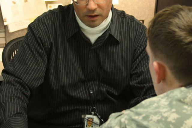 Robert Bozgoz (left), a Veterans Affairs military service coordinator at Walter Reed Army Medical Center, discusses a claim with Cpl. Matthew Kinsey. In IDES, MSCs guide Soldiers through the VA portion of the disability evaluation process.