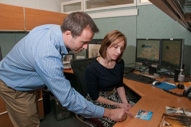 Shawn Bowman, HIO program manager, and Carrie Kilby, a registered nurse and health information specialist, review a deployment guide about Iraq. The HIO produces a wide array of materials, from information on how to protect against injuries to information on responding to earthquakes and other natural disasters.