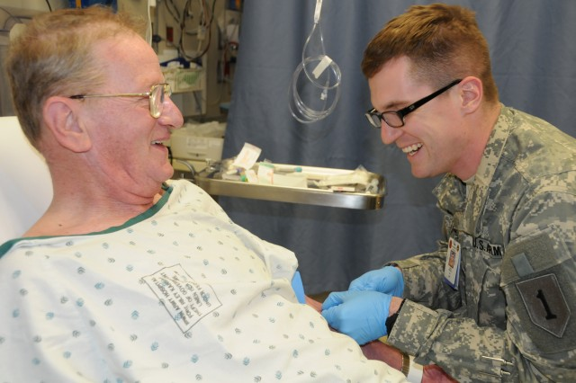 Pfc. Philip Gray, 5th Squadron, 4th Cavalry Regiment, 2nd Heavy Brigade Combat Team, 1st Infantry Division, Fort Riley, Kan., draws blood from Paul MacDonald, Army retiree and Irwin Army Community Hospital patient. Gray participated in the IACH emergency department medical proficiency training initial class recently.