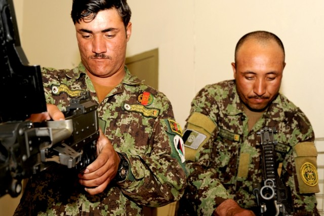 Sgt. Fazeli Abdol Aziz (left) and Sgt. Haidar Habibollah repair  M-240s at Camp Zafar, Herat, Afghanistan, April 26. The 207th Afghan National Army Corps received their first issued weapons repair kits from coalition forces and can now perform maintenance their own weapons.