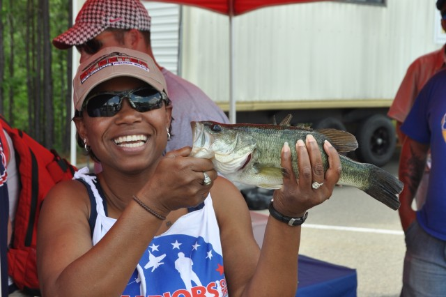 """Sgt. 1st Class Catina Taylor, crisis action team noncommissioned officer, U.S. Army Forces Command G1, proudly shows off """"Buddy"""" - her only """"keeper"""" from the 6th Annual Warriors on the Water Military Appreciation Bass Fishing Tournament, April 29, 2011, at Jordan Lake, N.C.  Taylor was one of 150 joint service members who were taken out for a day of competitive angling by volunteer professional and recreational bass anglers from across the United States.  In strict accordance with the tournament's """"catch and release"""" protocol, Buddy was safely returned to the lake, helping to ensure the healthy survival of the species."""