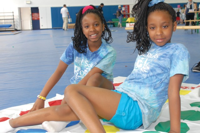 Twin sisters Alexia (left) and Alecia Dunlap, 9, pause for a photo during a game of Twister at the Child, Youth and School Services Springfest April 23 on Patch Barracks.