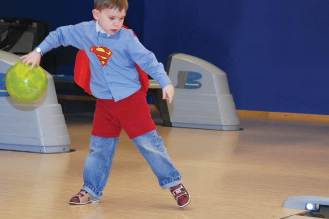 "Nolan Wilson, 5, dressed as ""Superboy"" lines up his shot at a ""Superhero Bowling"" event, hosted April 15 by the Galaxy Bowling and Entertainment Center on Panzer Kaserne as part of the Month of the Military Child festivities."