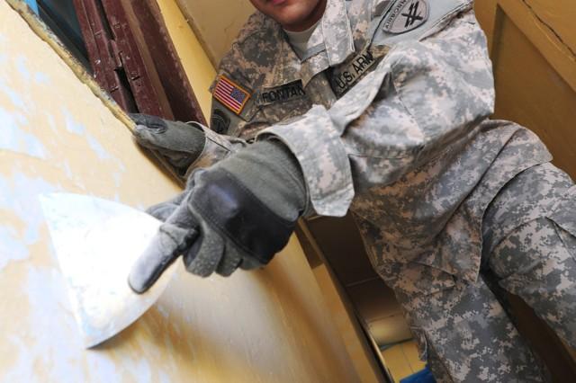 Spc. Alexis Fontan, 402nd Civil Affairs Battalion Team member, scrapes old paint from a Dikhil High School wall April 19, 2011.