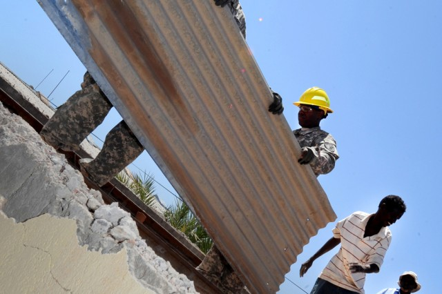Staff Sgt. Angel Vasquez (left) and Spc. Luis Alamo, 402nd Battalion Civil Affairs Team, work with Djiboutian volunteers to remove old roofing from the Dikhil High School April 19, 2011.