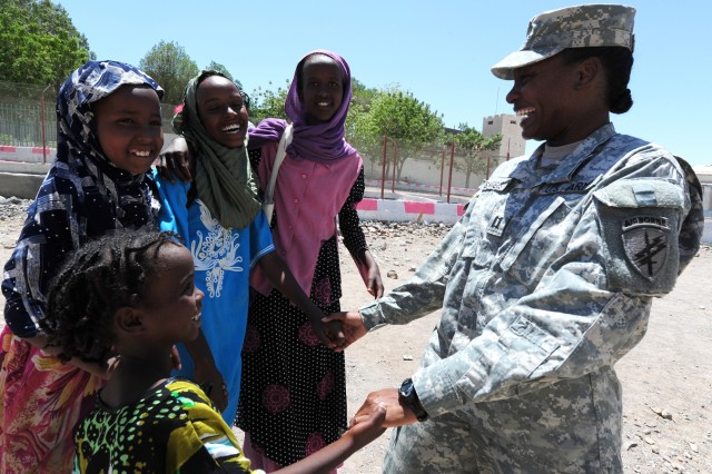 Capt. Courtney Sanders, 402nd Civil Affairs Battalion, makes friends with a group of girls in front of the Dikhil High School April 19, 2011.